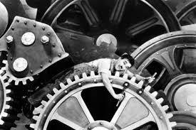 Charles Chaplin e cena clássica do filme Tempos Modernos